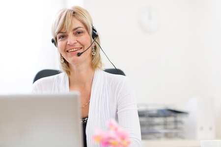 old center: Happy senior business woman with headset working on laptop