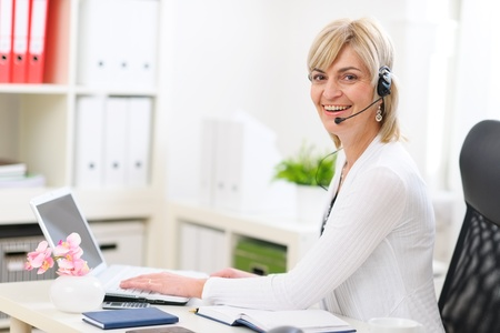 Happy senior business woman with headset working at office Stock Photo - 12637796