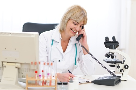 Smiling senior doctor woman speaking phone at office photo
