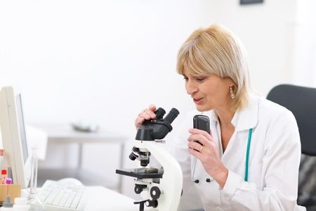 Senior doctor woman looking in microscope and making voice notes photo