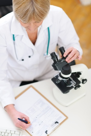 Closeup on researcher working with microscope and making notes in clipboard photo
