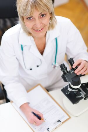 Senior researcher woman working with microscope and making notes in clipboard photo