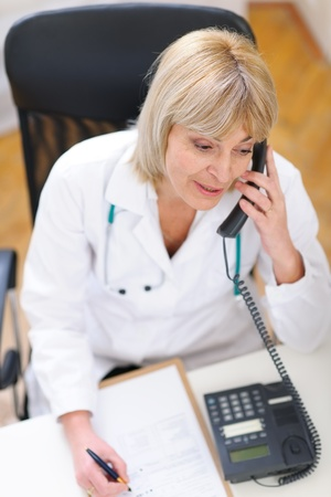 doctor office: Senior doctor speaking phone