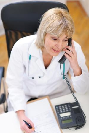 Senior doctor speaking phone Stock Photo - 12637841