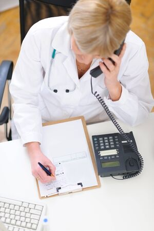 Doctor woman speaking phone and making notes in clipboard photo