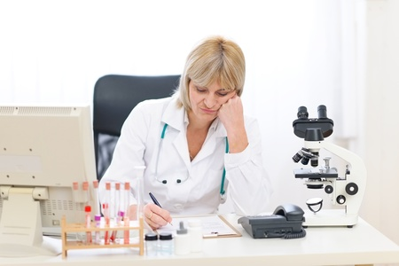 tedium: Bored senior doctor woman working at office