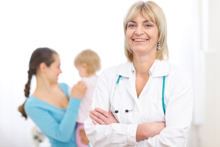 Portrait of senior pediatric doctor and mother with baby in background Stock Photo - 12637843