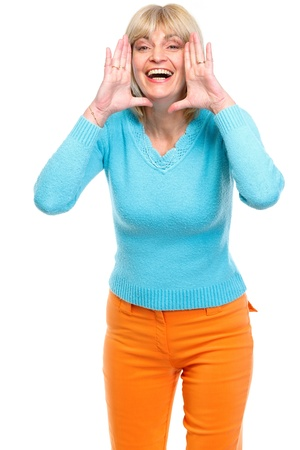Happy senior woman shouting through megaphone shaped hands photo