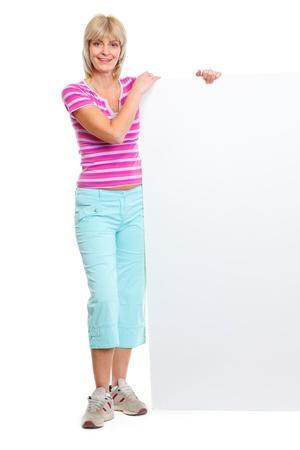 Full length portrait of smiling elderly woman holding blank billboard photo