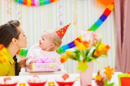 Mother giving birthday present for baby photo