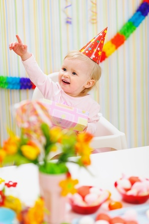 Baby with birthday gift pointing in corner Stock Photo - 12930580