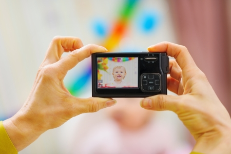 Closeup photo camera on mothers hands making birthday photos Stock Photo - 12930589