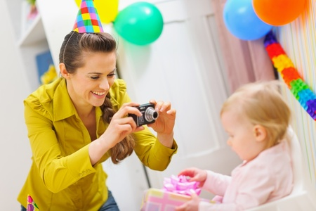 Mother making photos at babies birthday party photo