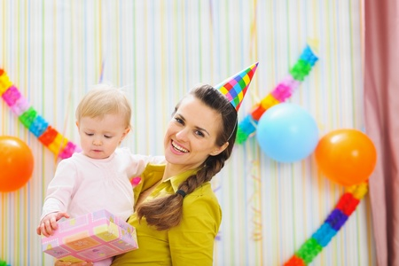 Portrait of happy mom and baby with birthday gift photo