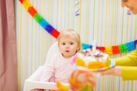 Mom carries cake for surprised baby photo