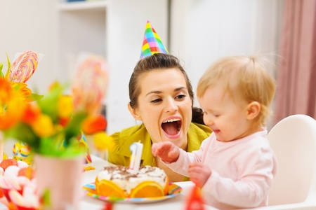 first birthday: Mother and baby having fun at birthday party