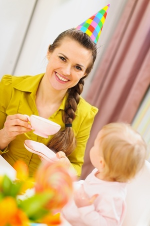 Mother drinking tea on babies birthday party Stock Photo - 12930726