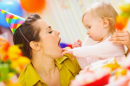 eat smeared baby: Beb� la madre de la alimentaci�n con torta de cumplea�os Foto de archivo