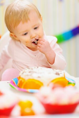 eat smeared baby: Eat smeared baby eating birthday cake Stock Photo