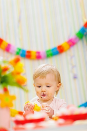Eat smeared baby eating orange at birthday party photo