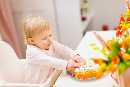 eat smeared baby: Eat smeared baby touched birthday cake by hands