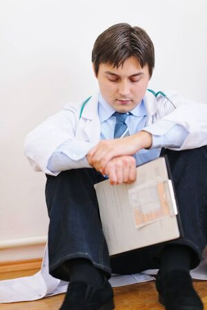 Upset male medical doctor sitting on floor photo