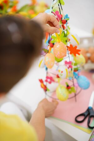 Closeup on female hands making Easter decoration photo