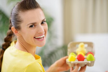 Happy woman holding tray with colorful Easter eggs photo