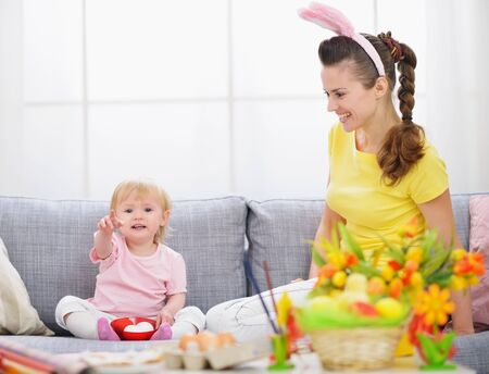 Mother and baby making preparations for Easter photo