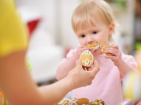 easter cookie: Mother giving baby cookie in shape of Easter egg. Focus on cookie