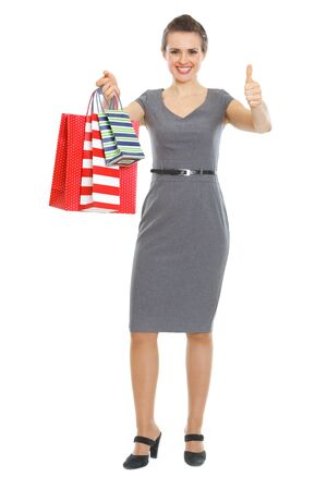 Happy elegant woman with shopping bags showing thumbs up photo