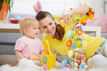 Mother and baby making Easter decoration photo