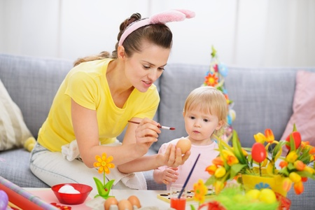Mother showing baby how to paint on Easter egg