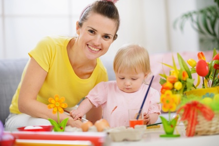 Happy mother helping baby painting on Easter eggs photo