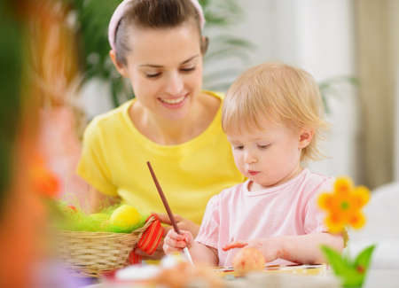 Mom helping baby painting on Easter eggs Stock Photo - 13008785