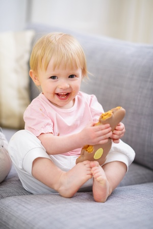 easter cookie: Happy baby eating Easter rabbit cookie Stock Photo