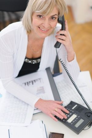 Smiling middle age business woman making phone call photo