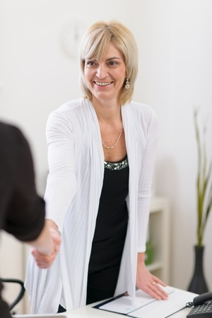 Smiling senior business woman shaking visitors hand photo