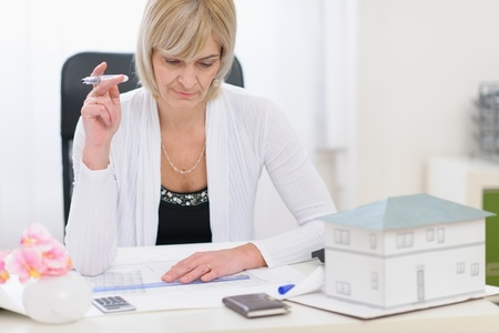 centrality: Middle age architect woman working on plans Stock Photo