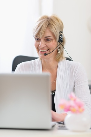 Happy senior business woman with headset working on laptop Stock Photo - 13087751