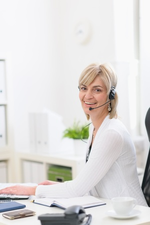 Happy middle age business woman with headset working at office photo