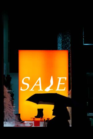 passerby: Silhouette of a passerby on storefront with sale inscription
