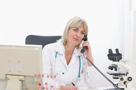 Smiling middle age doctor woman speaking phone at office photo
