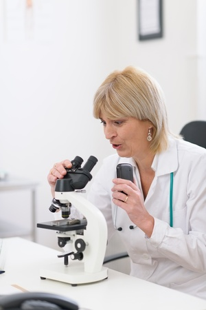 Surprised middle age doctor woman looking in microscope and making voice notes Stock Photo - 13087823