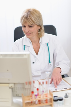 Portrait of smiling middle age doctor woman working on computer photo