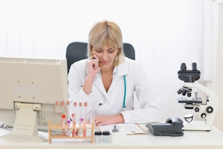 Concentrated middle age doctor woman working at office photo