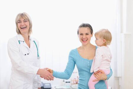 medical practice: Happy mother holding baby and shaking hand to pediatric doctor