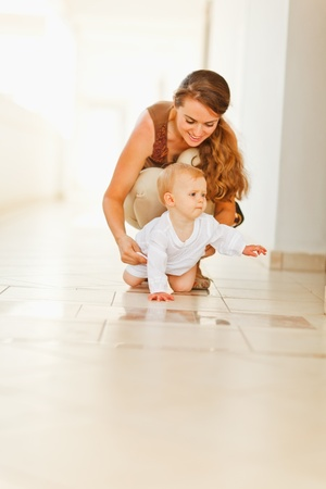 Happy mother helping baby to creep Stock Photo - 13115908