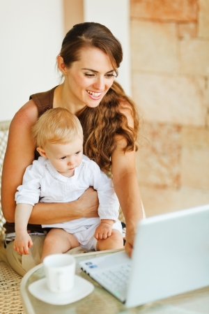 Young mother working with baby on laptop photo