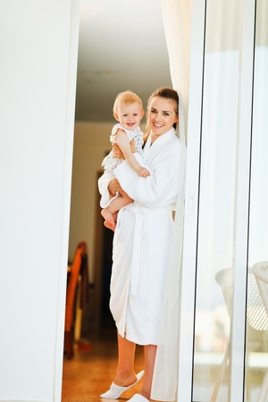 Smiling mother in bathrobe with baby looking out from window Stock Photo - 13116030